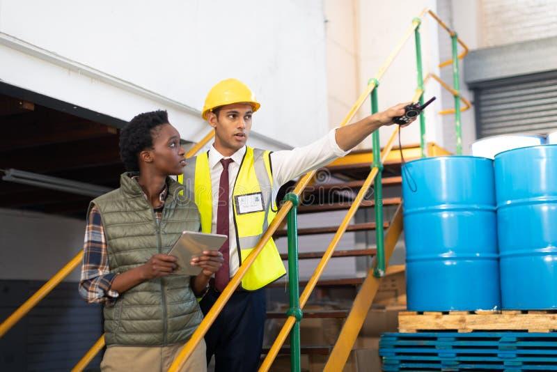 Manlig arbetsledare med den kvinnliga arbetaren som pekar avstånd i lager arkivfoton