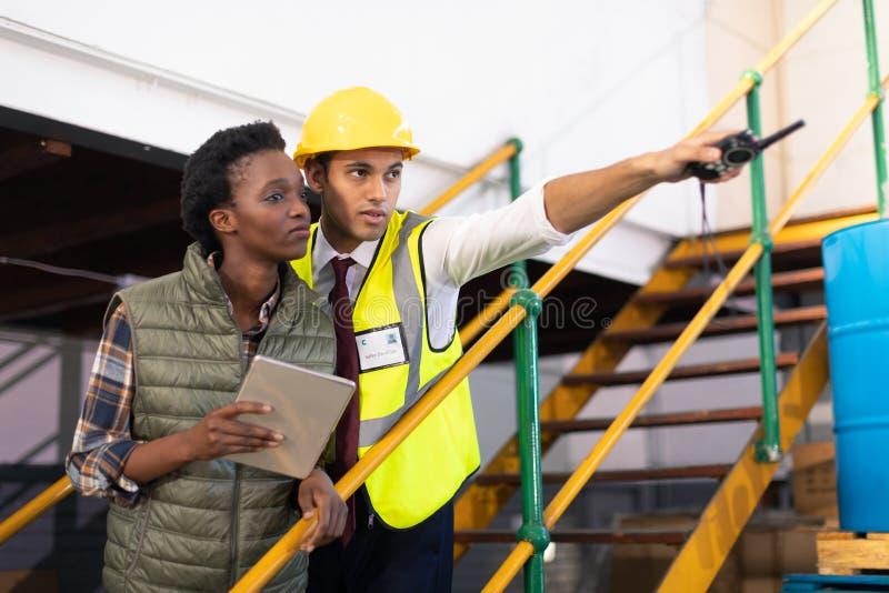 Manlig arbetsledare med den kvinnliga arbetaren som pekar avstånd i lager royaltyfri bild