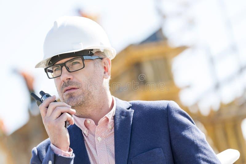 Manlig arbetsledare som använder walkie-talkie på konstruktionsplatsen royaltyfri foto
