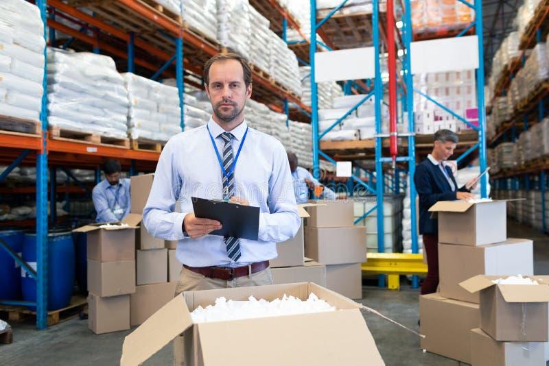 Manlig arbetsledare som ser kameran, medan kontrollera materiel i lager royaltyfri foto