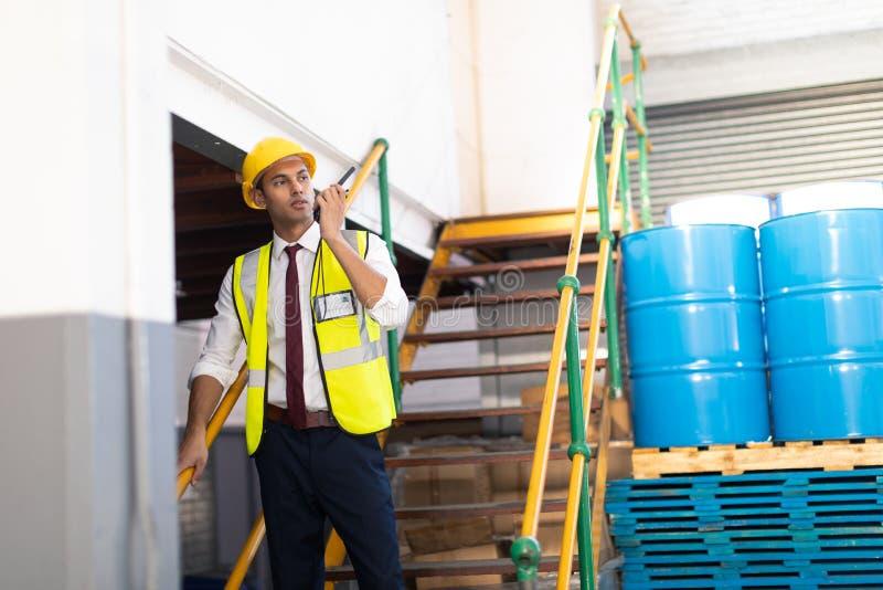 Manlig arbetsledare som talar på walkietalkie på trappa i lager fotografering för bildbyråer