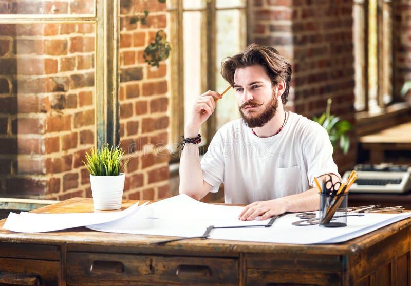 Manlig arkitekt With Draft och blyertspenna som i regeringsställning studerar plan royaltyfria foton