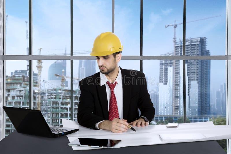 Manlig arkitekt som arbetar med ritningar i kontoret arkivbilder
