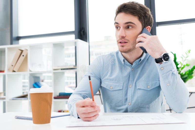 manlig arkitekt som arbetar med ritningen och talar på smartphonen arkivfoto