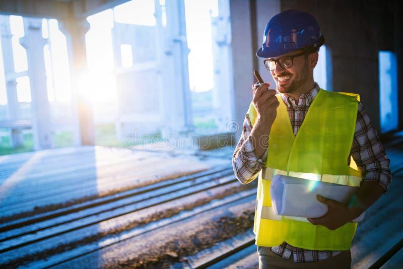 Manlig arkitekt som meddelar på walkie-talkie på platsen royaltyfri bild