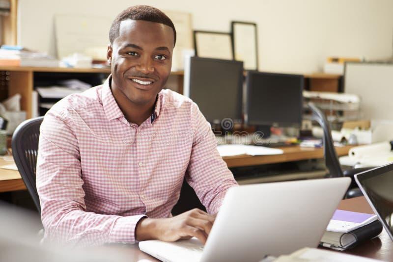 Manlig arkitekt Working At Desk på bärbara datorn arkivbild