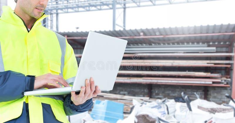 Manlig arkitektur genom att använda bärbara datorn på konstruktionsplatsen arkivbild