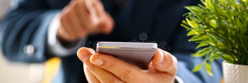 Manlig arm i dräkthålltelefon royaltyfria foton