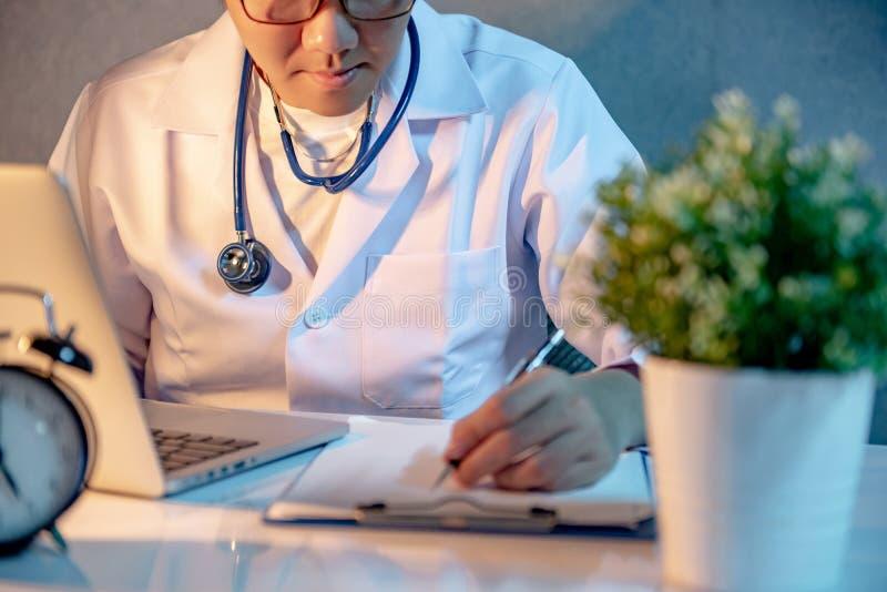 Manlig asiatisk doktor som arbetar med bärbara datorn och skrivplattan i sjukhus royaltyfri foto