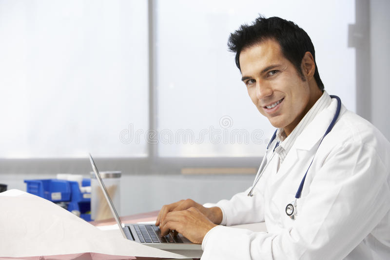Manlig bärbar dator för doktor In Surgery Using royaltyfria bilder