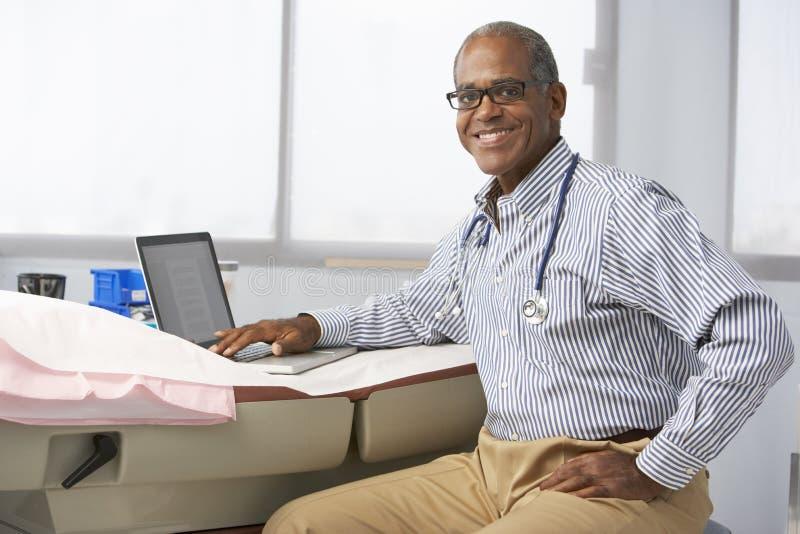 Manlig bärbar dator för doktor In Surgery Using arkivfoton