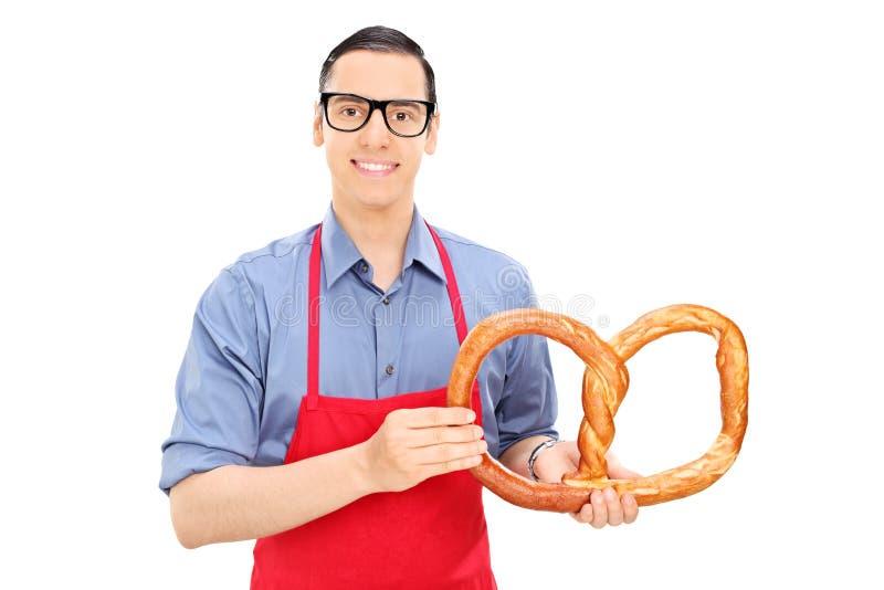 Manlig bagare som rymmer en enorm kringla royaltyfri bild