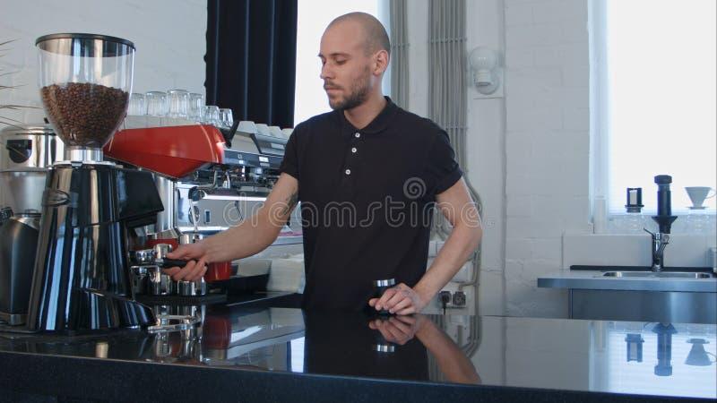 Manlig barista genom att använda kaffemaskinen som förbereder kaffe för en klient fotografering för bildbyråer