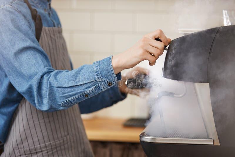 Manlig barista i den enhetliga tvagningen som bryggar grejer genom att använda ångaren royaltyfri bild