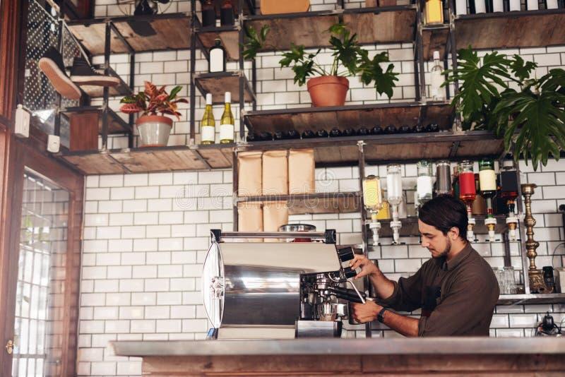 Manlig barista som gör en kopp kaffe arkivbild