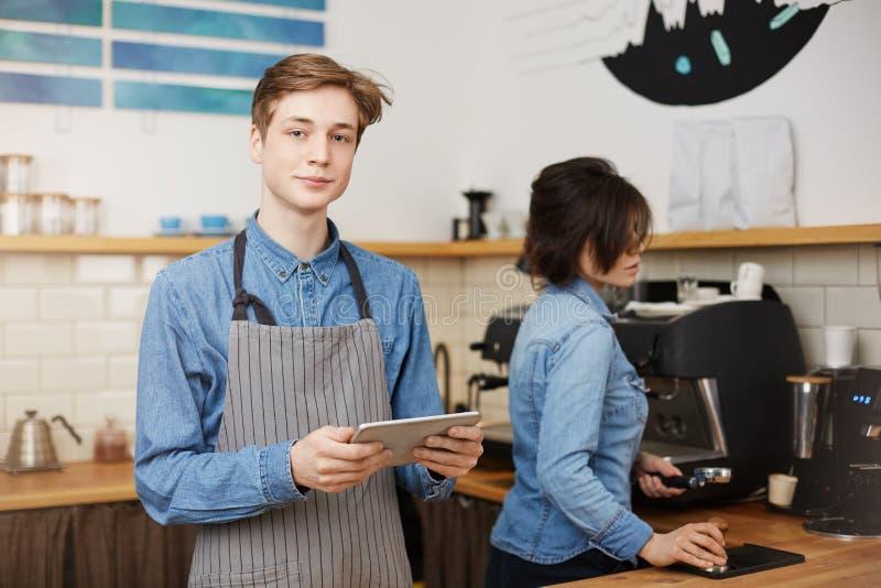 Manlig barista som tar beställning, hållande flik, kvinnligt baristadanandekaffe arkivbild