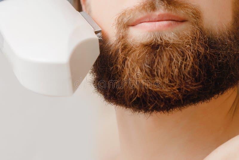 Manlig behandling för tillvägagångssätt för skägg och för mustasch för borttagning för depilationlaser-hår i salong royaltyfri foto