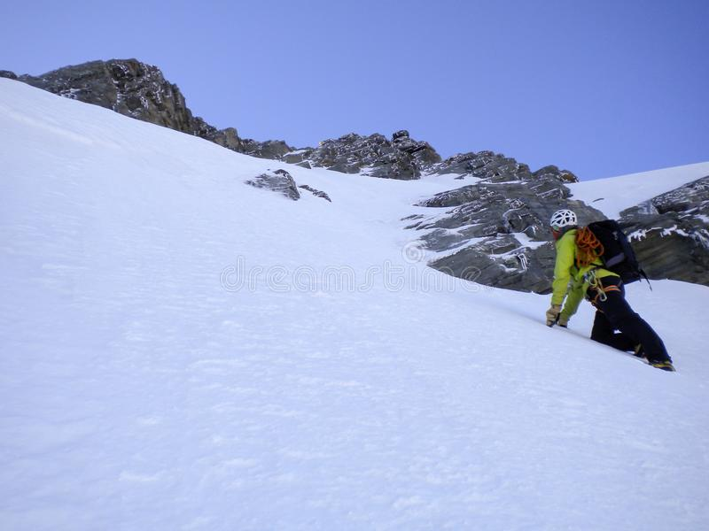 Manlig berghandbok som klättrar en brant snöcouloir på hans väg till en hög toppmöte i de schweiziska fjällängarna arkivbild