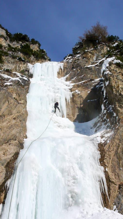 Manlig berghandbok som rappelling av en brant fryst vattenfall efter en isklättringutfärd fotografering för bildbyråer