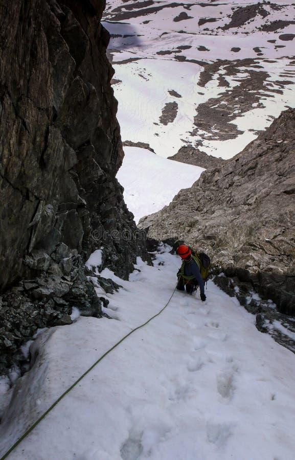 Manlig bergsbestigare i en mycket brant och smal gully på ett rep och att se ner arkivbilder