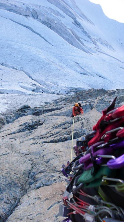 Manlig bergsbestigare på en utsatt klättringrutt som är hög ovanför en glaciär royaltyfria bilder