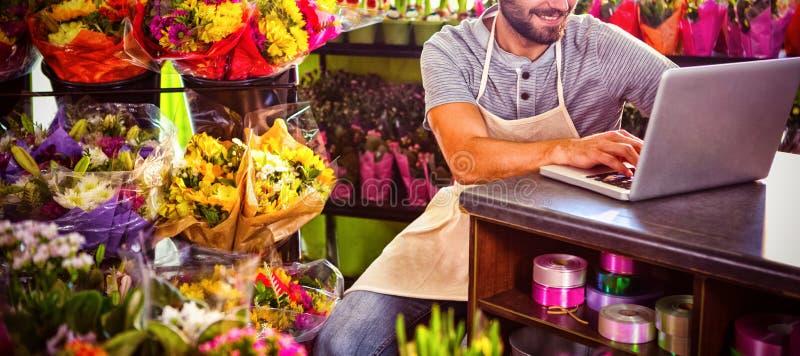 Manlig blomsterhandlare som använder bärbara datorn royaltyfri bild