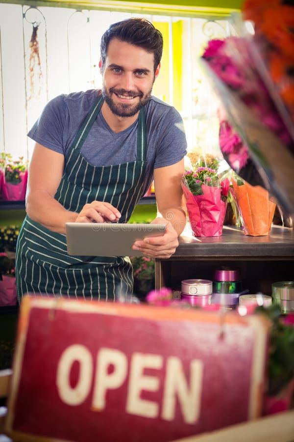 Manlig blomsterhandlare som rymmer den digitala minnestavlan på hans blomsterhandel royaltyfri foto