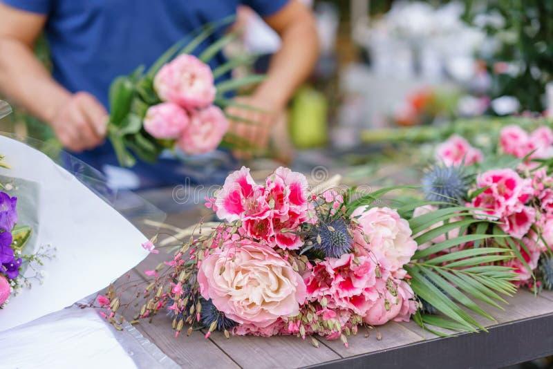Manlig blomsterhandlare som skapar den härliga buketten i blomsterhandel utomhus- arbete i blomsterhandel Manassistent eller ägar arkivbilder