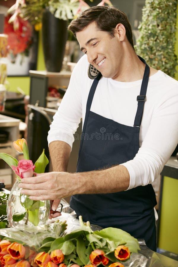 Manlig blomsterhandlareIn Shop Taking beställning över telefonen royaltyfri foto