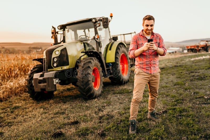 Manlig bonde som arbetar på fält genom att använda smartphonen i modernt jordbruk - traktor- och släpbakgrund royaltyfria foton