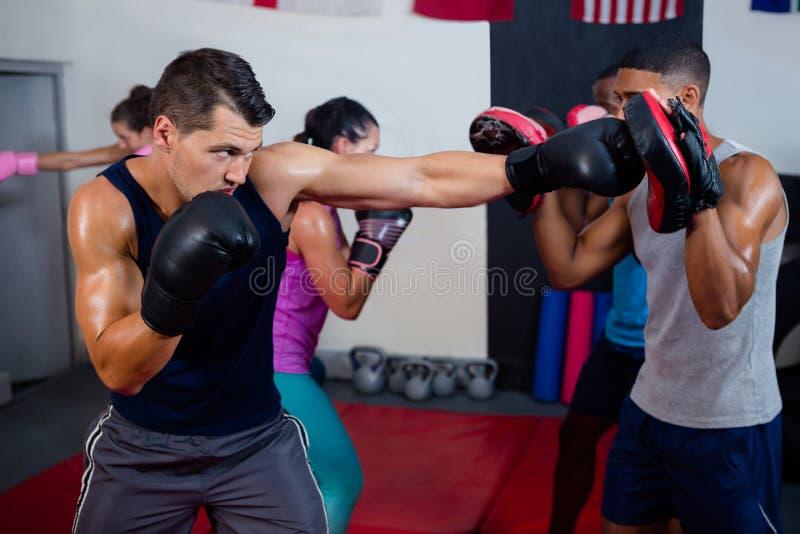 Manlig boxare och instruktör som öva med boxning royaltyfria foton