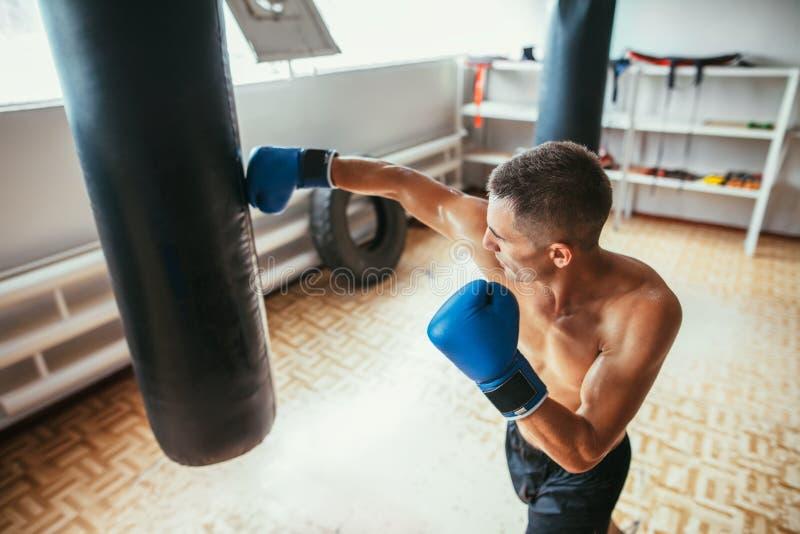 Manlig boxare som slår den stansa påsen på en boxas studio royaltyfri bild