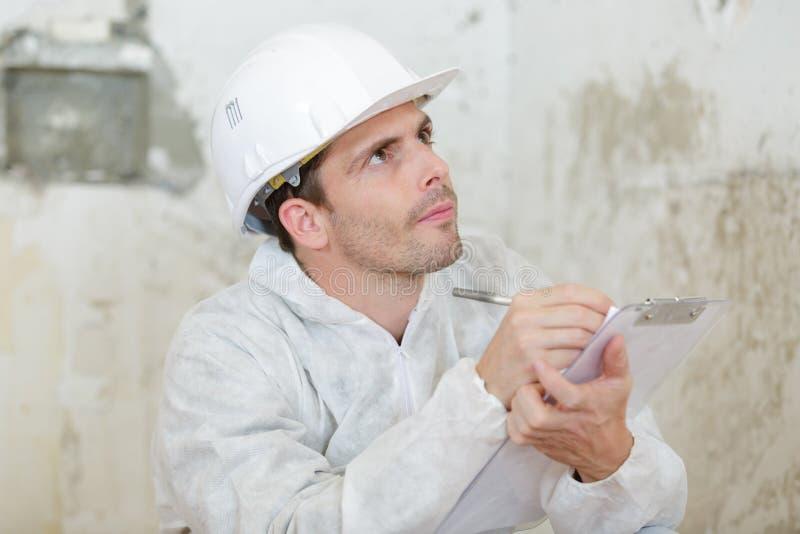 Manlig byggmästare eller manuell arbetare i hjälmhandstil på skrivplattan royaltyfria bilder