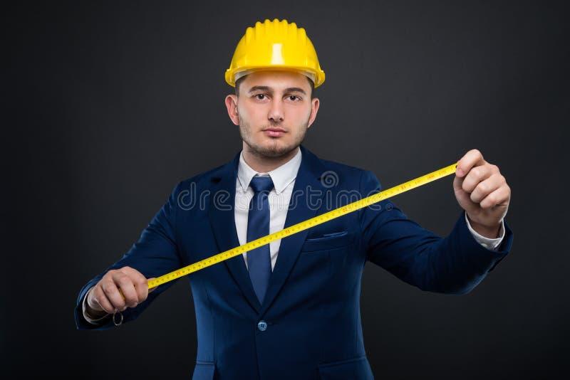 Manlig byggmästare med hjälmen som rymmer en meter royaltyfria bilder