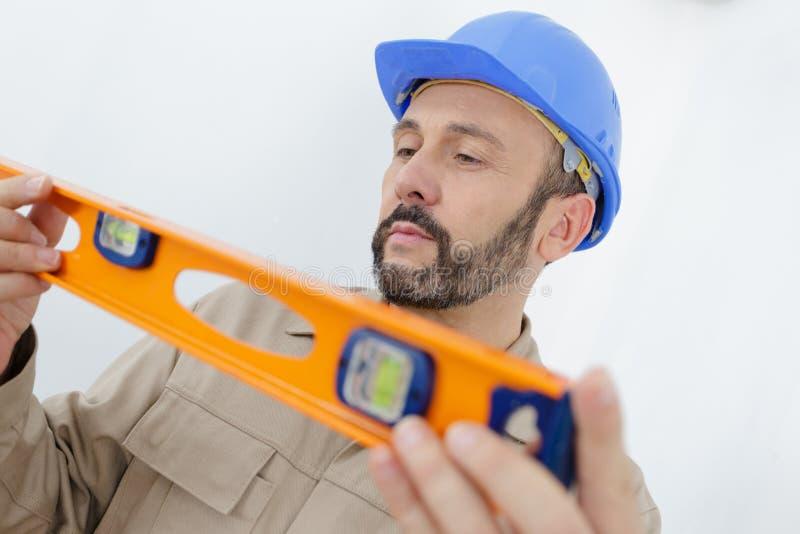 Manlig byggmästare som mäter väggen arkivfoto