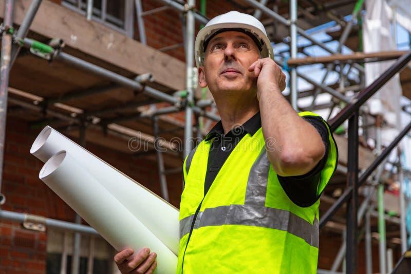 Manlig byggmästareordförande Architect på byggnadsplats genom att använda telefonen och arkivbild
