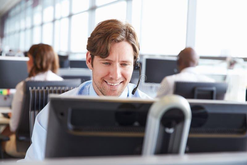 Manlig call centerarbetare som ser skärmen, närbild royaltyfri foto