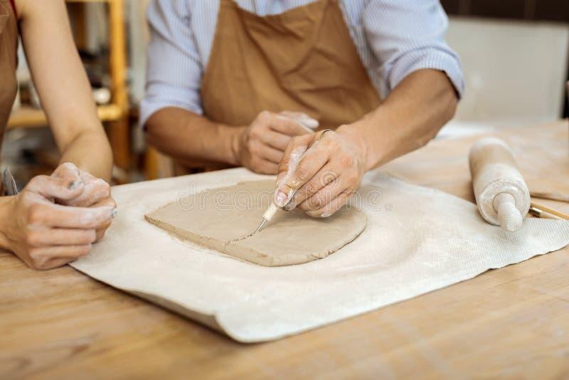 Manlig ceramist som hjälper hans kollega i danandevasmålning royaltyfri fotografi