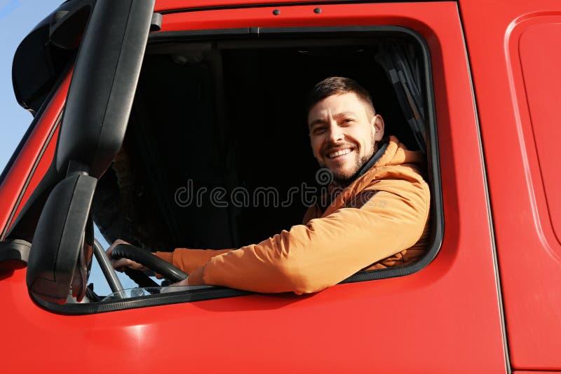 Manlig chaufför som ser ut ur lastbilen royaltyfri fotografi