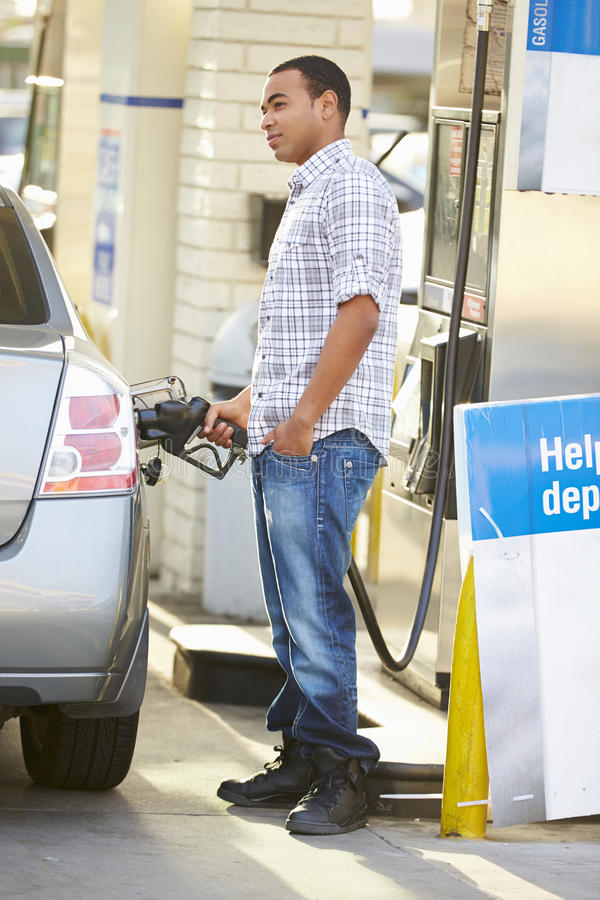 Manlig chaufförFilling Car At bensinstation arkivbild