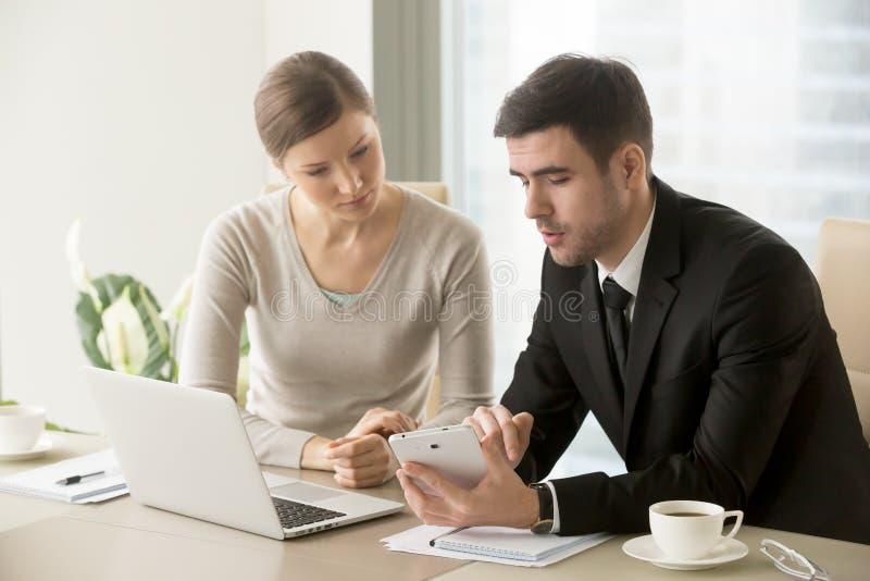 Manlig chef som förklarar uppgifter till kvinnlig anställd arkivfoton