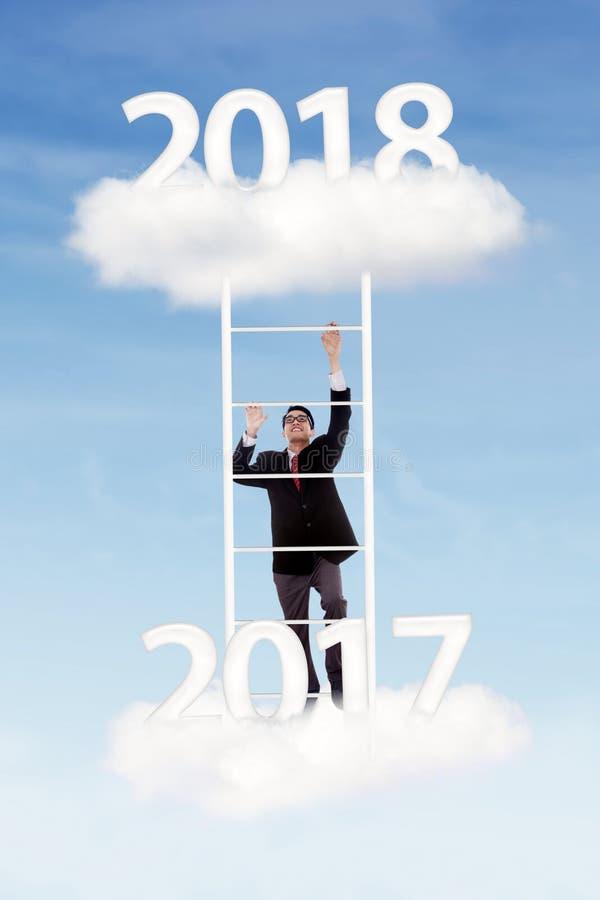 Manlig chef som klättrar det uppåtriktade numret 2018 royaltyfri foto