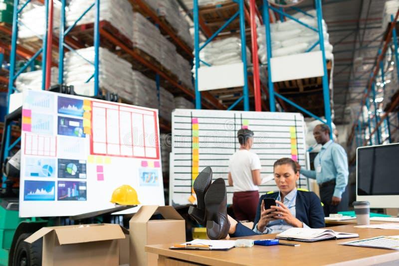 Manlig chef som kopplar av med fot upp, medan genom att använda mobiltelefonen på skrivbordet fotografering för bildbyråer