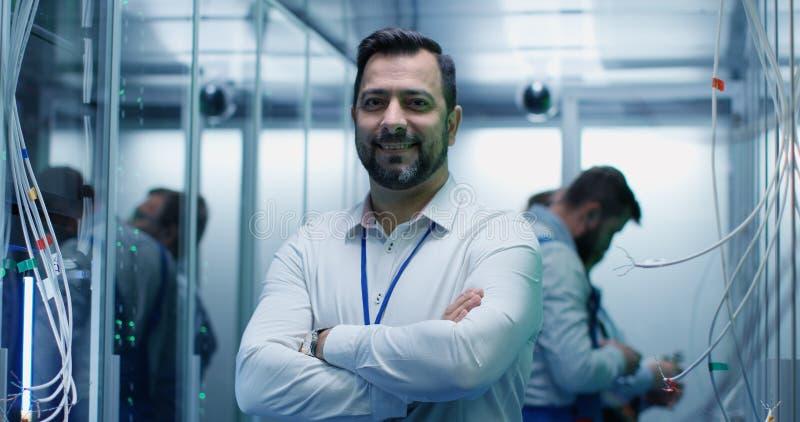 Manlig chef som ler i en datorhall arkivfoto