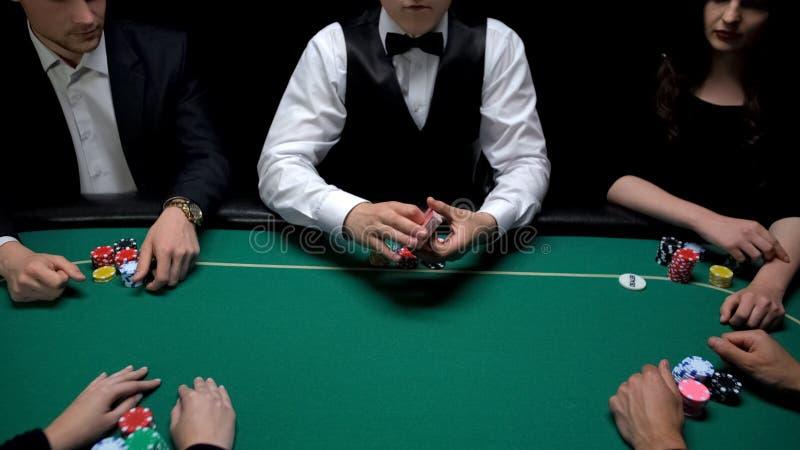Manlig croupier som rymmer kort klara att starta pokerleken på kasinot som spelar sportar arkivfoton