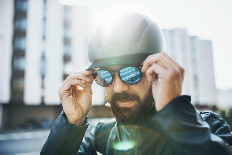 Manlig cykelkurir med hjälmen som sätter på solglasögon i stad arkivbild