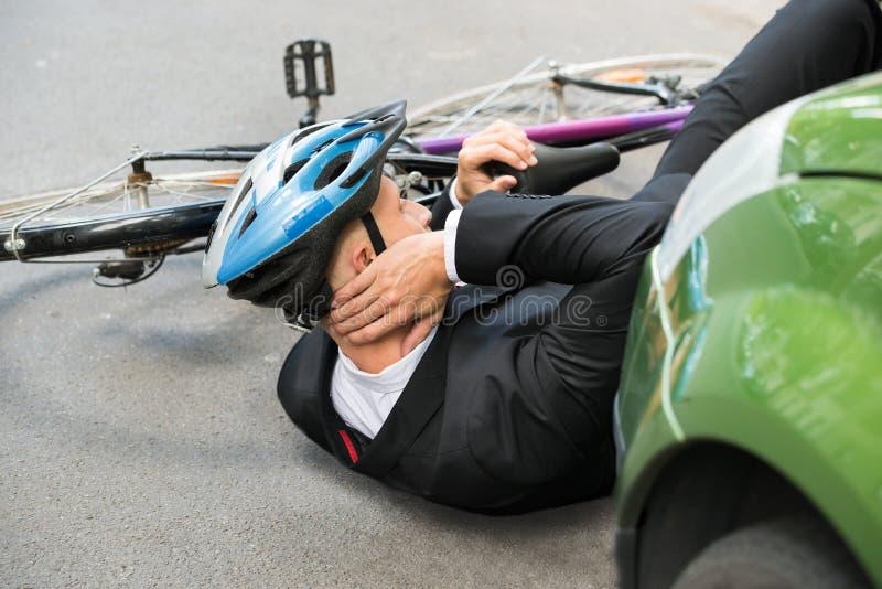 Manlig cyklist efter bilolycka arkivfoto