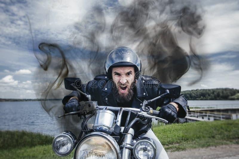 Manlig cyklist i hjälm på en motorcykel royaltyfria bilder