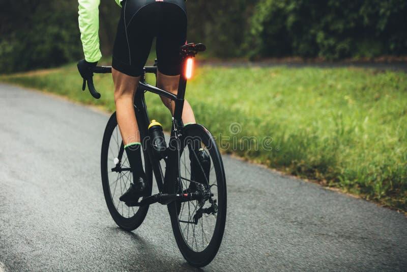 Manlig cyklist som öva på en våt väg fotografering för bildbyråer