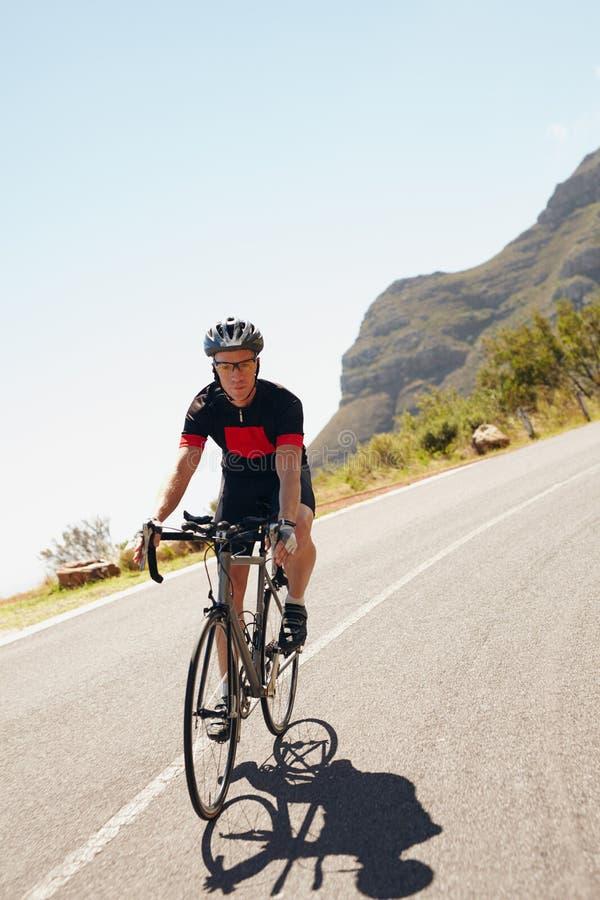 Manlig cyklist som rider ner en landsväg fotografering för bildbyråer